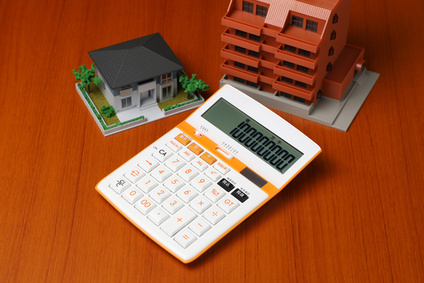 calculator and house building miniature models on the table
